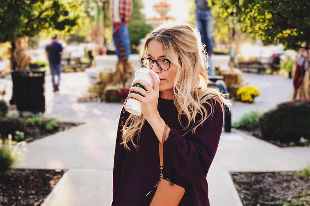 woman at park sipping on starbucks drink
