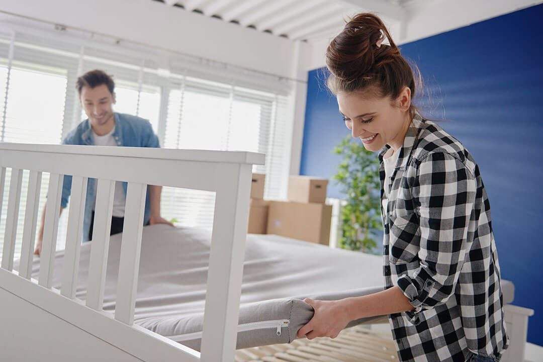 Young couple putting new mattress on bed
